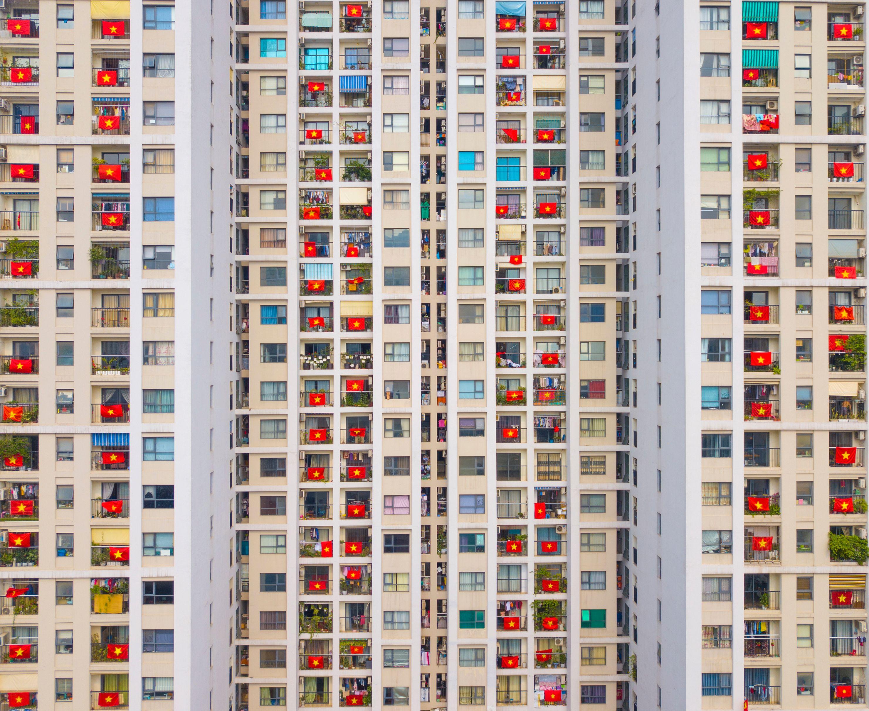 Жители многоквартирного дома выражают сочувствие исолидарность, вывешивая национальный флаг Вьетнама насвоих балконах во время пандемии коронавируса. Ханой, Вьетнам, 22 апреля 2020