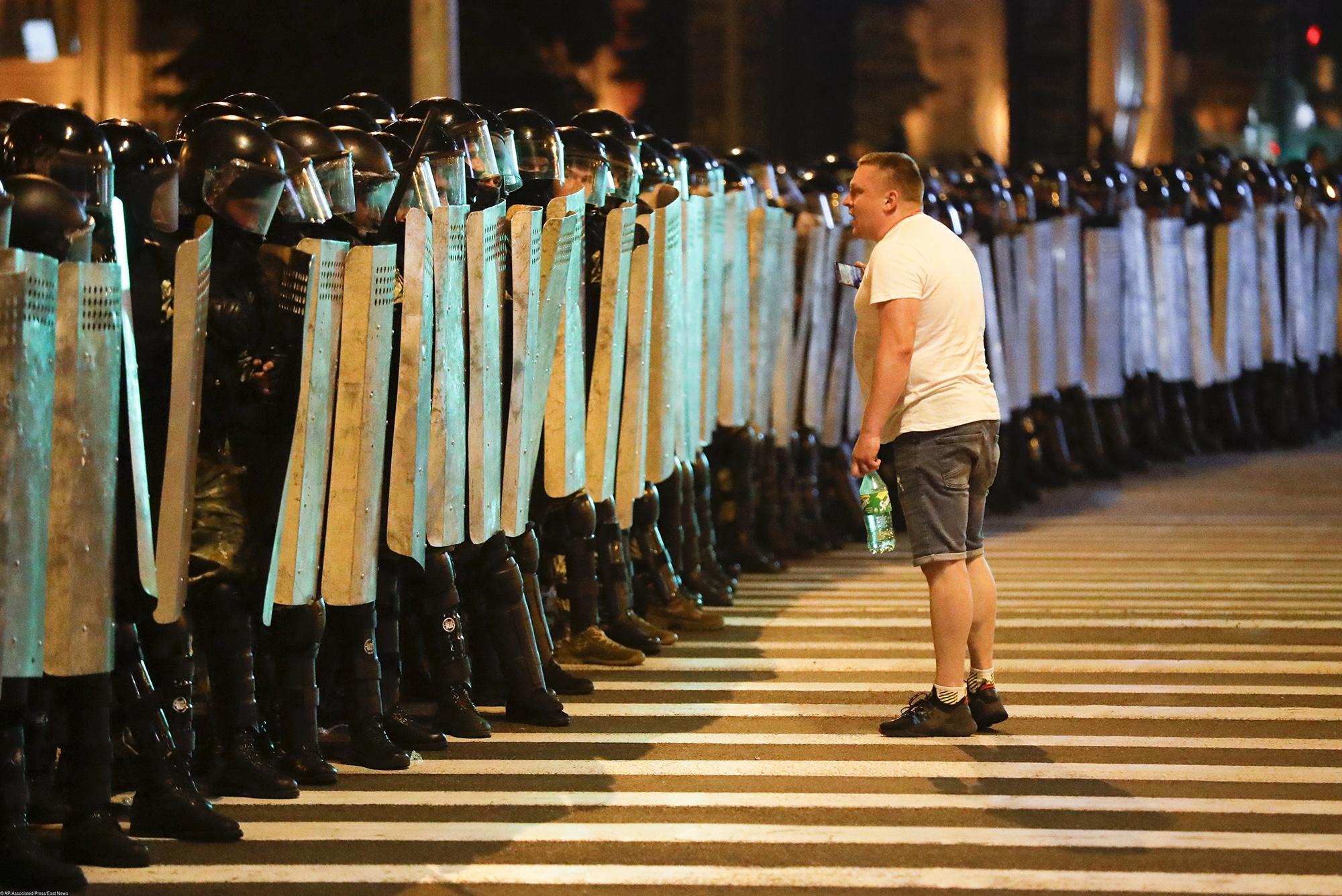 Один изпротестующих говорит что-то полицейским во время митингов вМинске, Беларусь