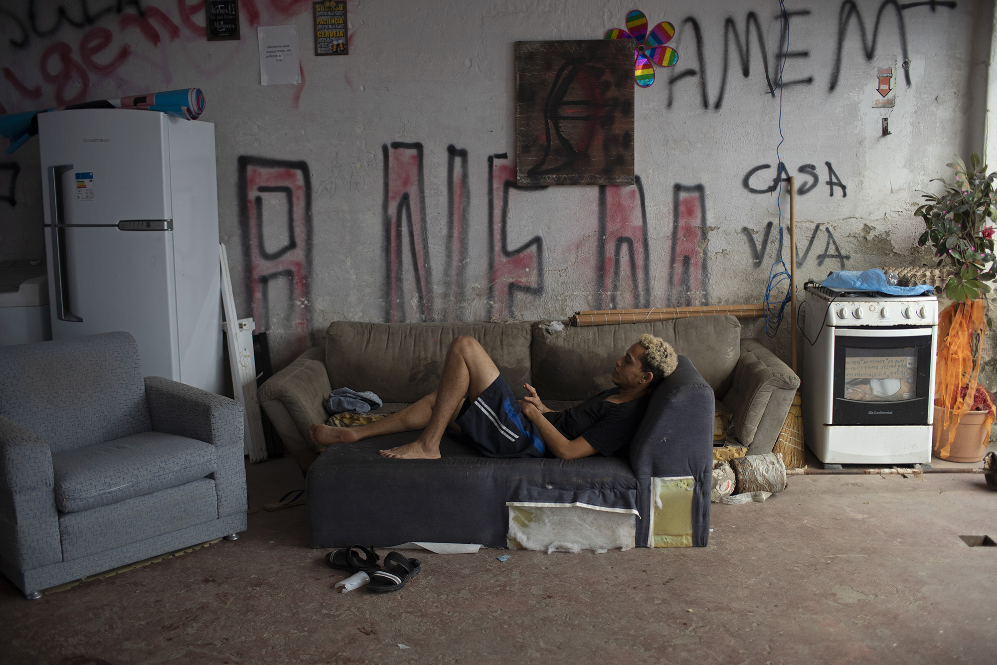Transgender Igor rests on a couch in the courtyard of the squat known as Casa Nem, in Rio de Janeiro, Brazil, Wednesday, July 8, 2020. The six-floor building is home to members of the LGBTQ commuity riding out the pandemic behind closed doors. (AP Photo/Silvia Izquierdo)