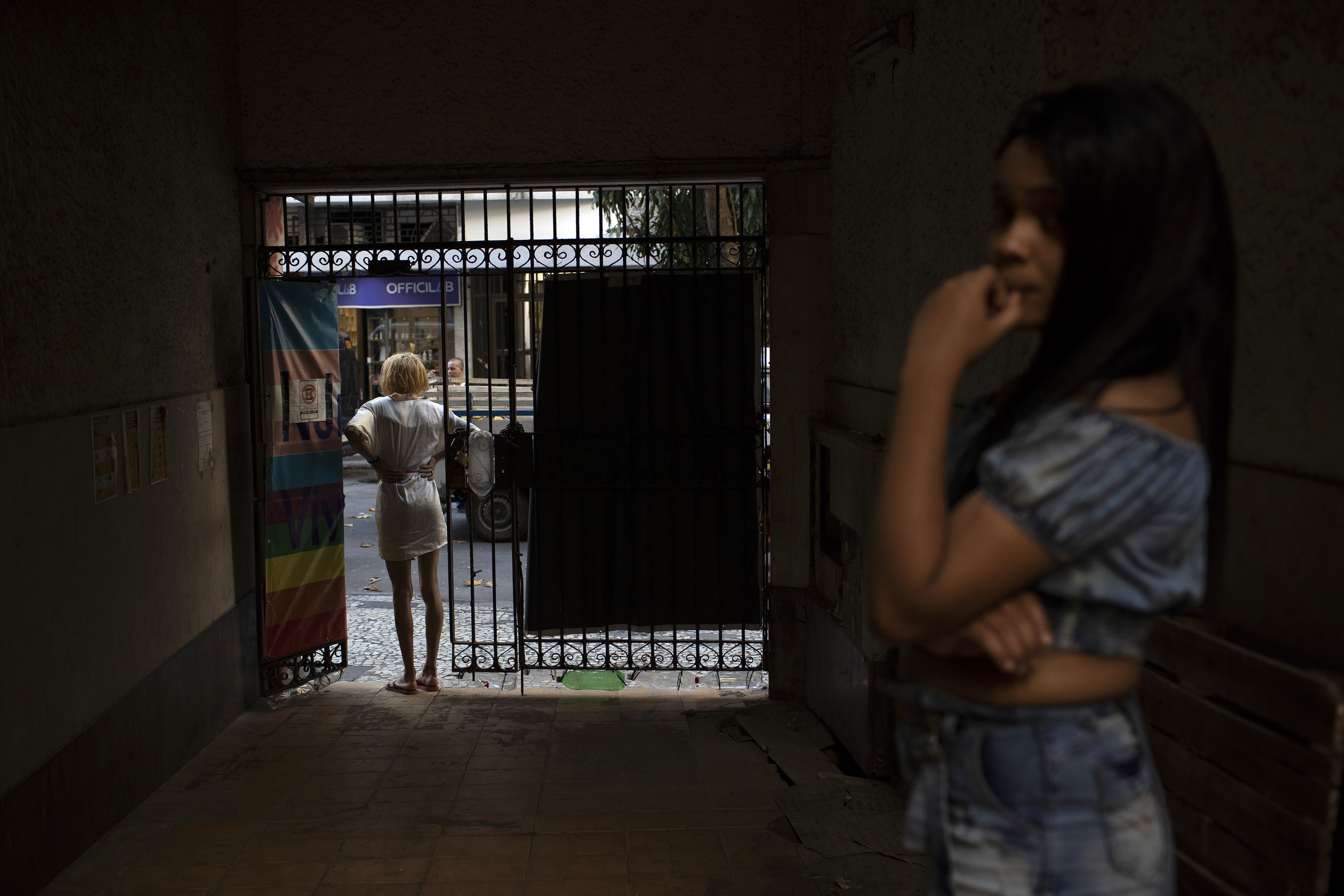 A resident of the squat Casa Nem waits at the entrance for a delivery of donated furniture, in Rio de Janeiro, Brazil, Wednesday, July 8, 2020. The six-floor building is home to members of the LGBTQ community riding out the pandemic behind closed doors.