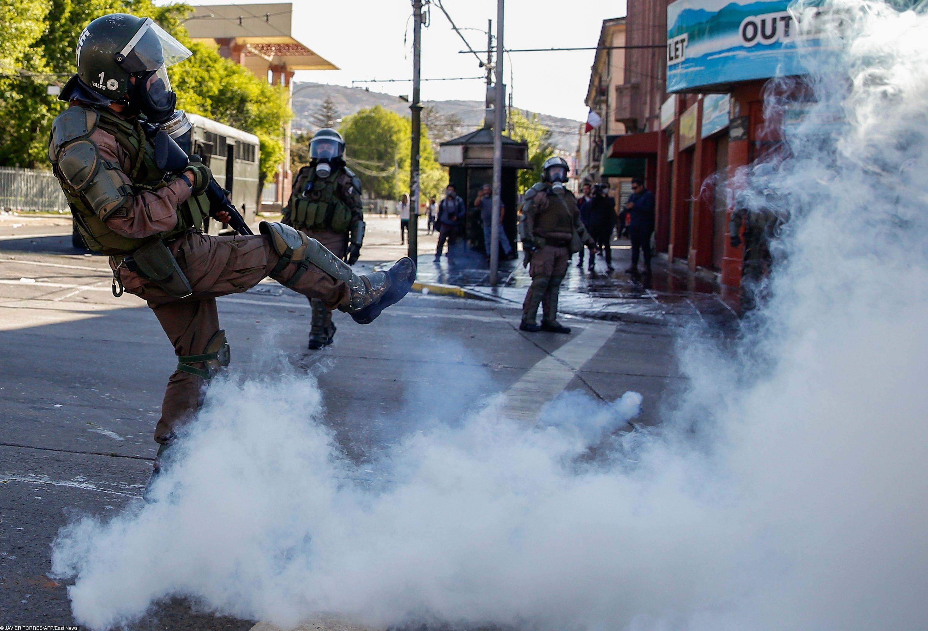 Riot policemen clash with demonstrators during protests in Valparaiso, Chile, on October 20, 2019. - Fresh clashes broke out in Chile's capital Santiago on Sunday after two people died when a supermarket was torched overnight as violent protests sparked by anger over economic conditions and social inequality raged into a third day.