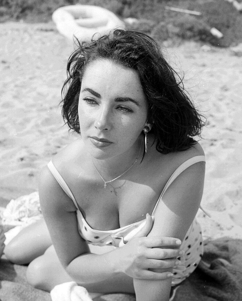 Актриса Элизабет Тейлор позирует фотографу напляже вМалибу, штат Калифорния, 4 июля 1956 года