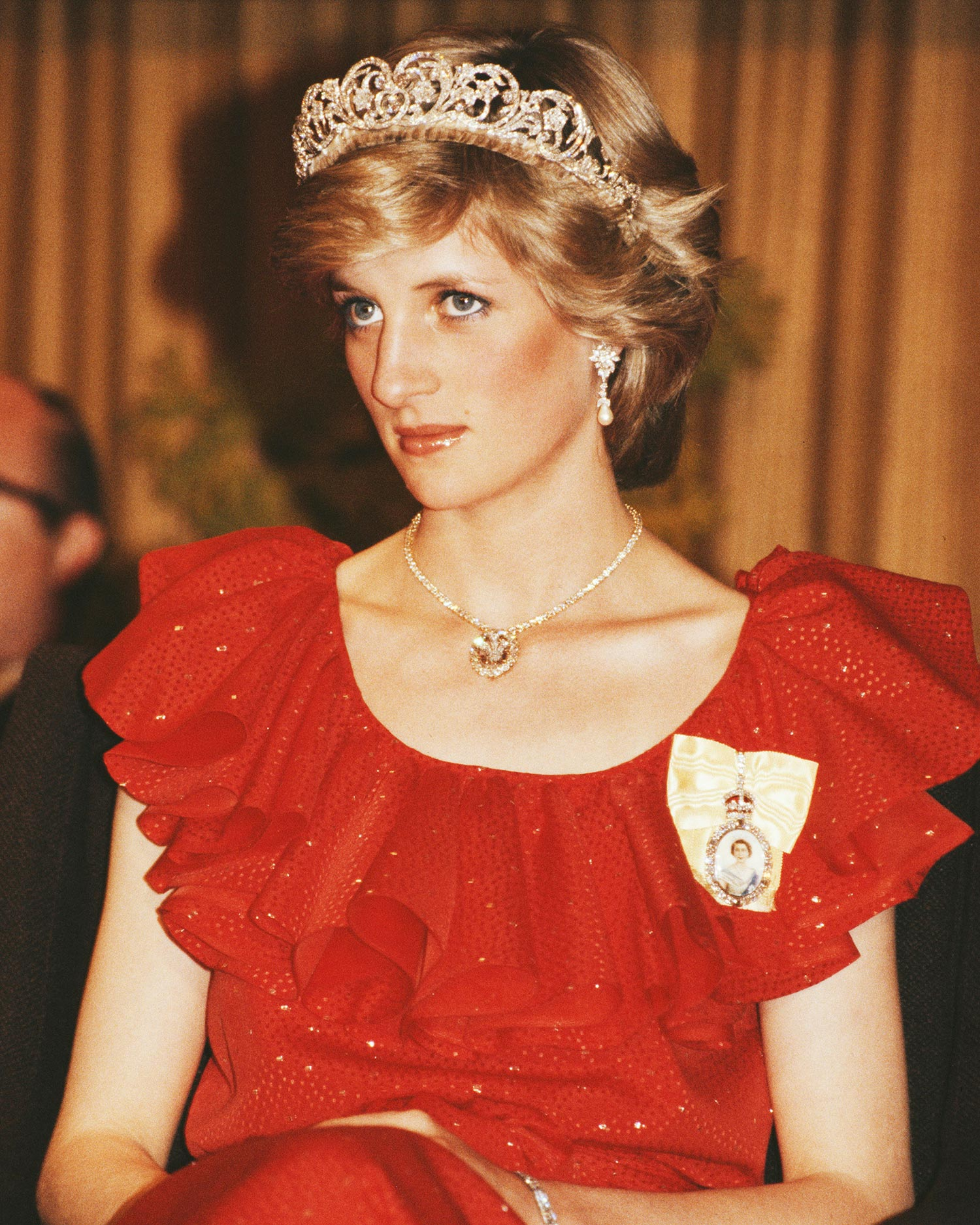 Diana, Princess of Wales (1961 - 1997) wearing a red Bruce Oldfield gown to a state reception at the Wrest Point Federal hotel in Hobart, Tasmania, 30th March 1983. She is wearing the Spencer family tiara and the badge of the Royal Family Order of Elizabeth II, and has restyled the Prince of Wales feathers brooch as a necklace. Her pearl and diamond earrings were a gift from the Emir of Qatar. (Photo by Tim Graham Photo Library via Getty Images)