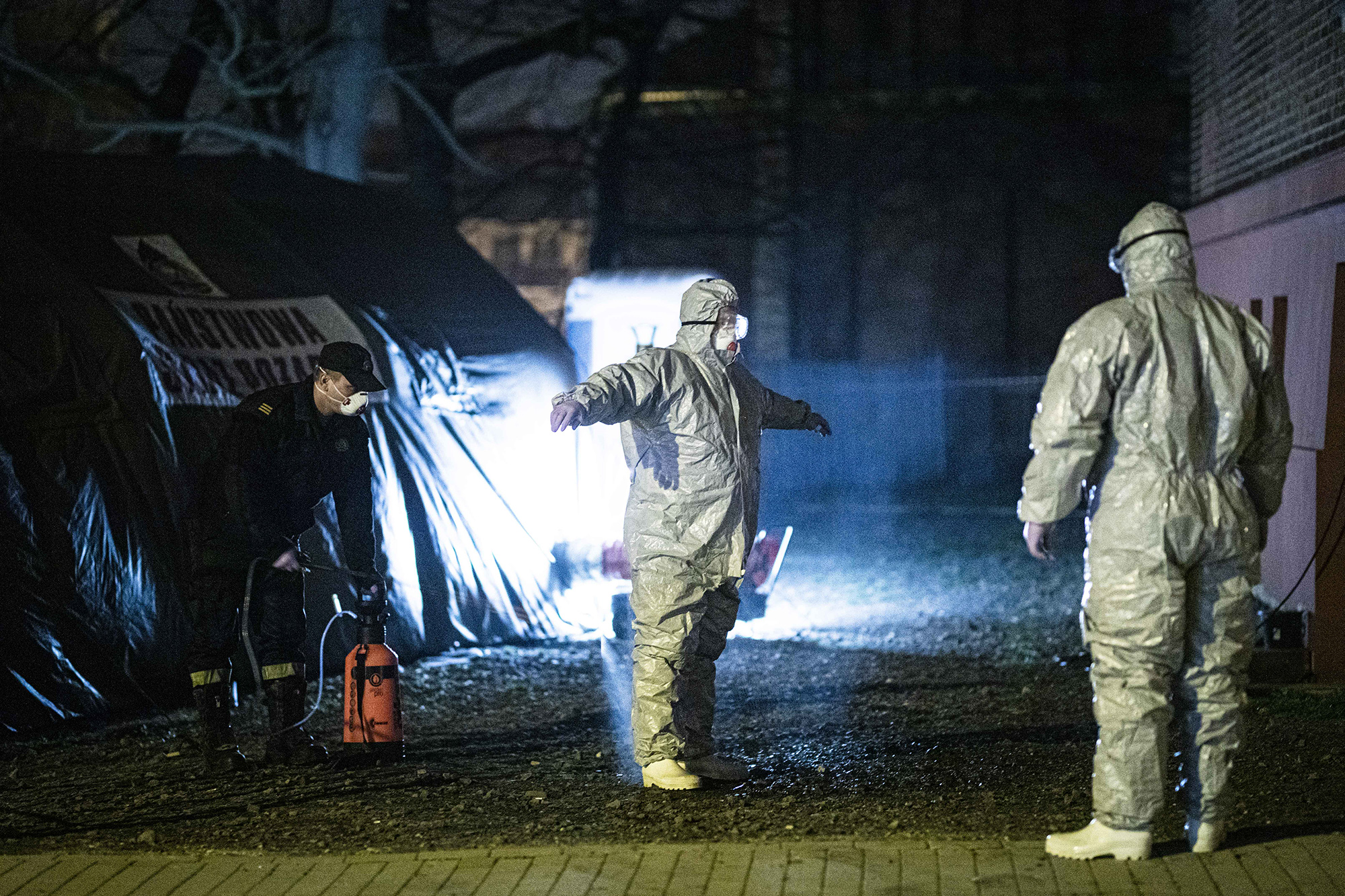 ZGORZELEC, POLAND - MARCH 14: Two men with protective clothing become disinfected after checking people crossing the german-polish border on March 14, 2020 in Zgorzelec, Poland. Poland and Czech Republic decide to close the border at the night from 14th to 15th of March to Germany trying to stop spreading of Corona virus. (Photo by Florian Gaertner/Photothek via Getty Images)