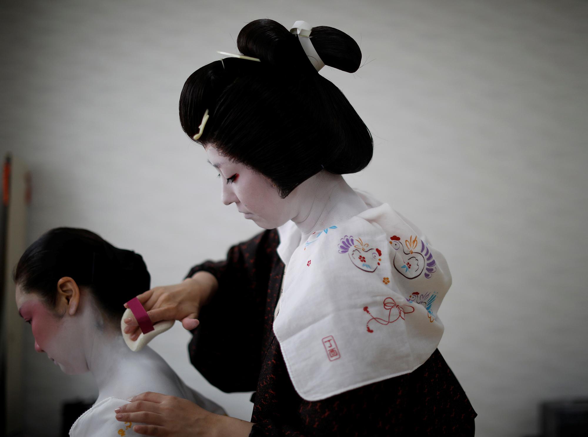 Коику раскрашивает шею Майю — так они вдоме гейш Икуко готовятся кработе навечеринке.
