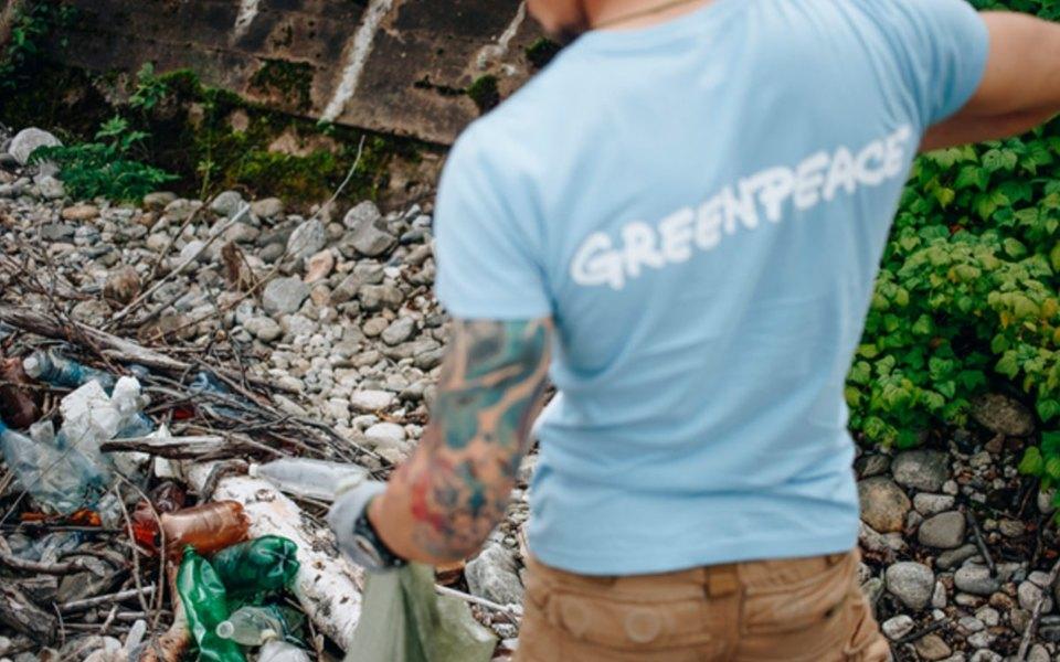 Волонтер Greenpeace собирает мусор на берегу Байкала